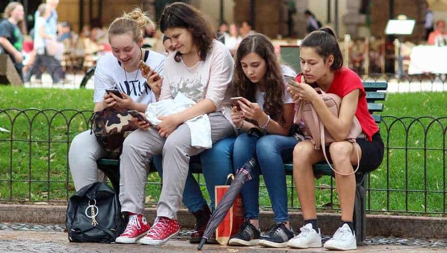 Shopping Party - Teen girls using smartphones on bench