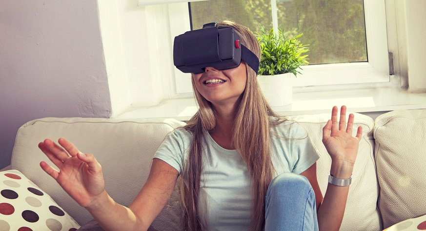 Virtual reality shopping - young woman on couch with VR headset