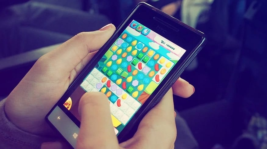 Mobile game revenue - person playing game on smartphone
