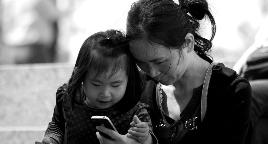 Apple use in China - woman and child looking at iPhone