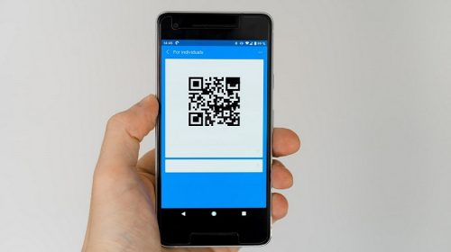 QR code adoption - person holding phone displaying QR code