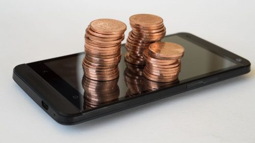 Mobile commerce sales - pennies on top of phone